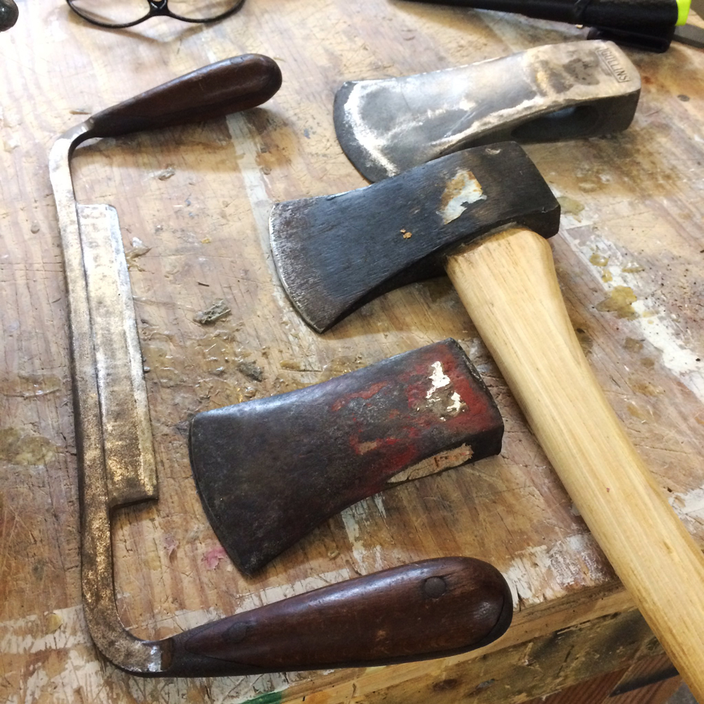 Three axes and a draw knife being prepared for restoration